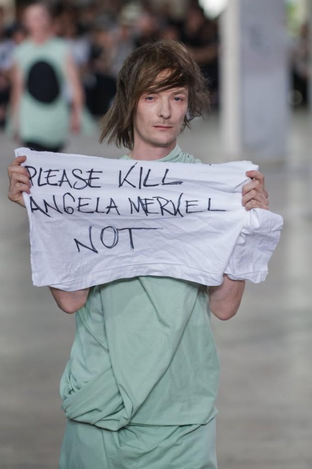 Sem avisar, modelo protesta contra Angela Merkel durante desfile do estilista Rick Owens, em Paris. Crédito:Kamil Zihnioglu/AP