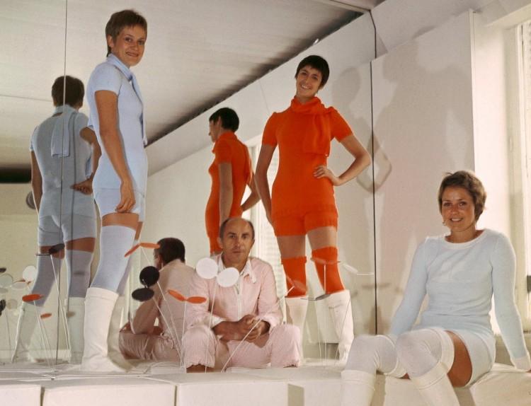 O estilista André Courrèges, em 1976. Ele está rodeado por modelos que trajam sua coleção de alta-costura. Crédito: AFP