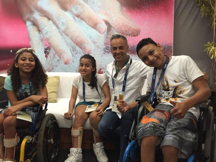 O estilista Francisco Costa e crianças que participarão da abertura da Paraolimpíada. Ele criou figurinos funcionais para a cerimônia. Crédito: Divulgação